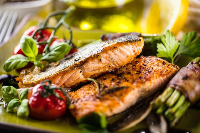 Salmone grigliato con le verdure servite sul piatto di pietra verde sulla tavola di legno fotografia stock libera da diritti
