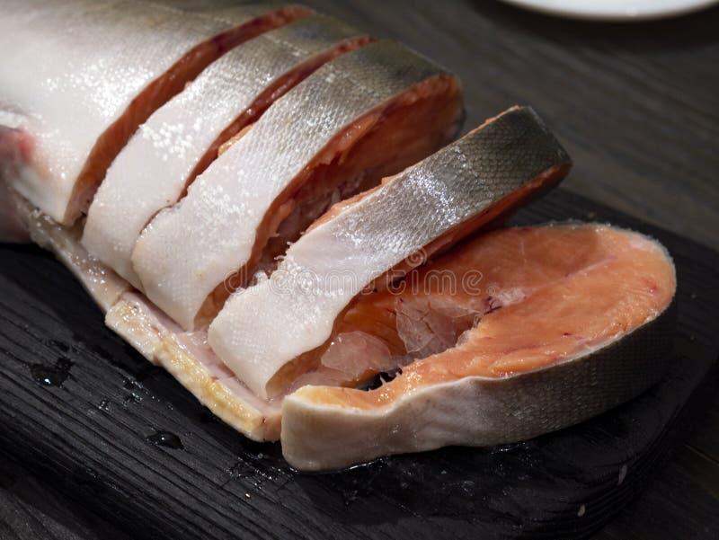 Salmone rosa su un tagliere, incidente le bistecche fotografia stock