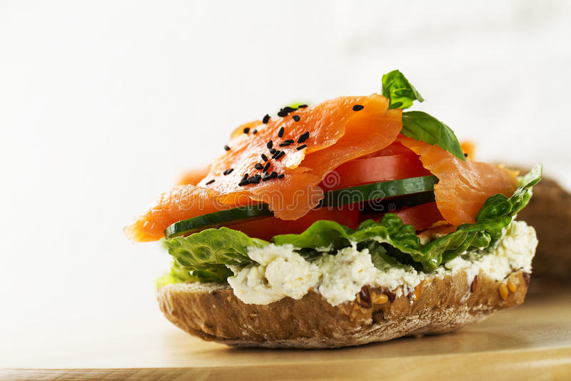 Salmone salato saporito variopinto con le verdure sul panino luminoso fotografie stock