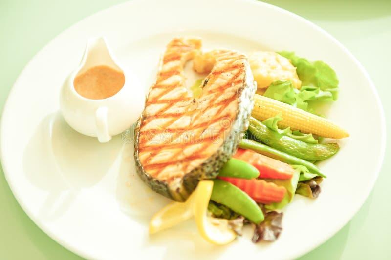 Salmones asados a la parrilla con el lim?n y la ensalada en la placa blanca, fondo verde borroso Luz del sol brillante Alimento s imagen de archivo