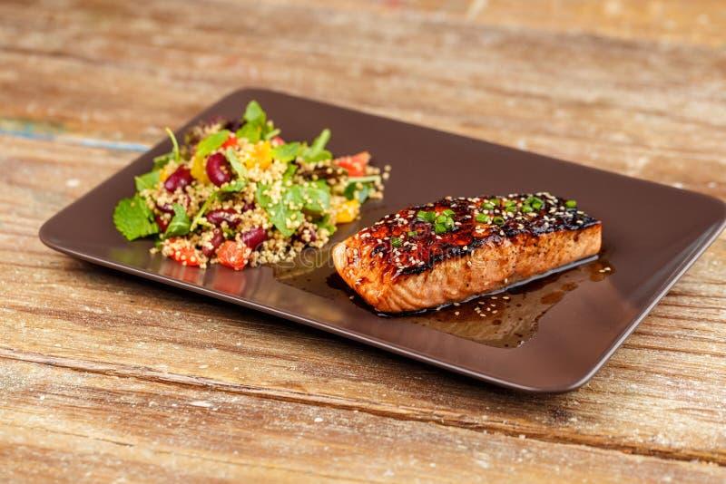 Salmones asados a la parrilla con la ensalada de la quinoa en la placa marrón imagenes de archivo