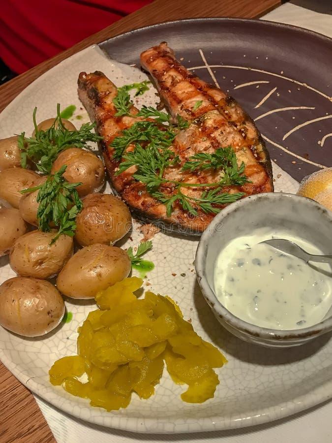 Salmones asados a la parrilla con las pequeñas patatas hervidas sin pelar imagen de archivo