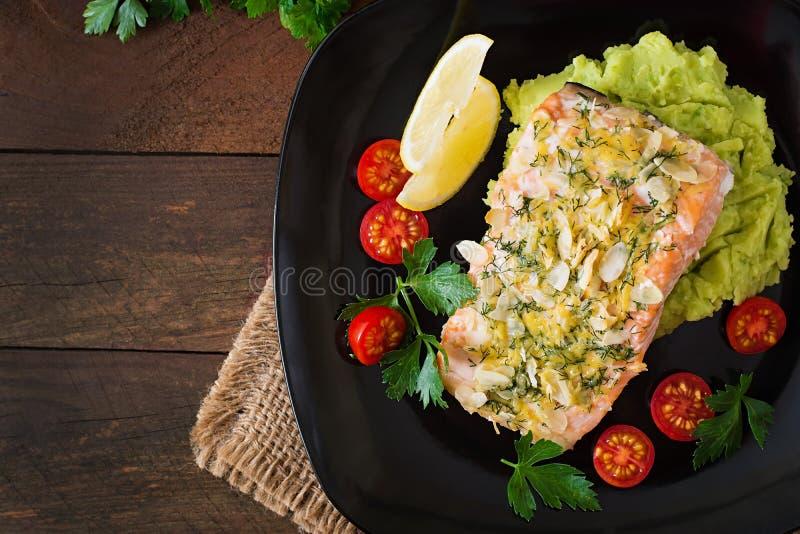 Salmones cocidos con queso y la almendra, con los purés de patata y los guisantes verdes foto de archivo libre de regalías