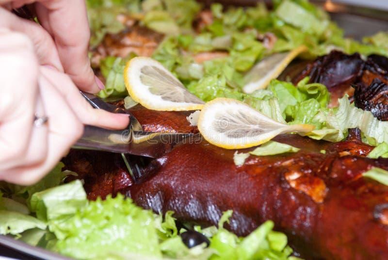 Salmones cocidos en hojas de la lechuga debajo de cuñas de limón Las manos femeninas sostienen un cuchillo y una bifurcación y co foto de archivo libre de regalías