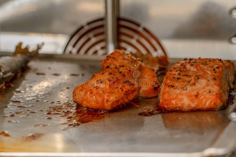 Salmones cocinados y otros pescados dentro de la opinión del horno Mariscos de color salmón adobados que asan a la parrilla dentr fotografía de archivo