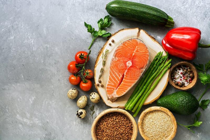 Salmones del filete de pescados crudos, cereales, verduras frescas, huevo de codornices, nueces y especias en un fondo gris Comid imágenes de archivo libres de regalías