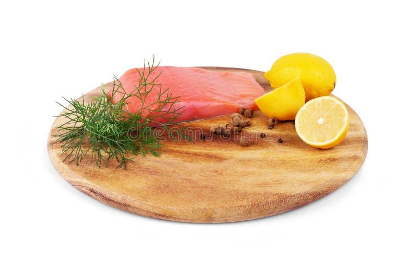 Salmones en tabla de cortar con los limones y las hierbas en un fondo blanco fotografía de archivo