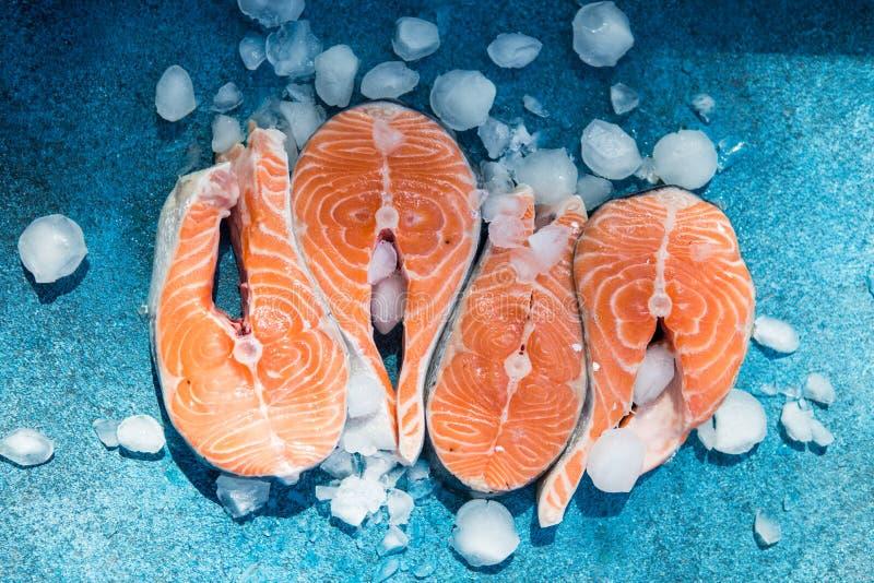 Salmones Filete de pescados rojo de la trucha cruda servido con las hierbas y el hielo en piedra azul Cocinar salmones, marisco C imágenes de archivo libres de regalías