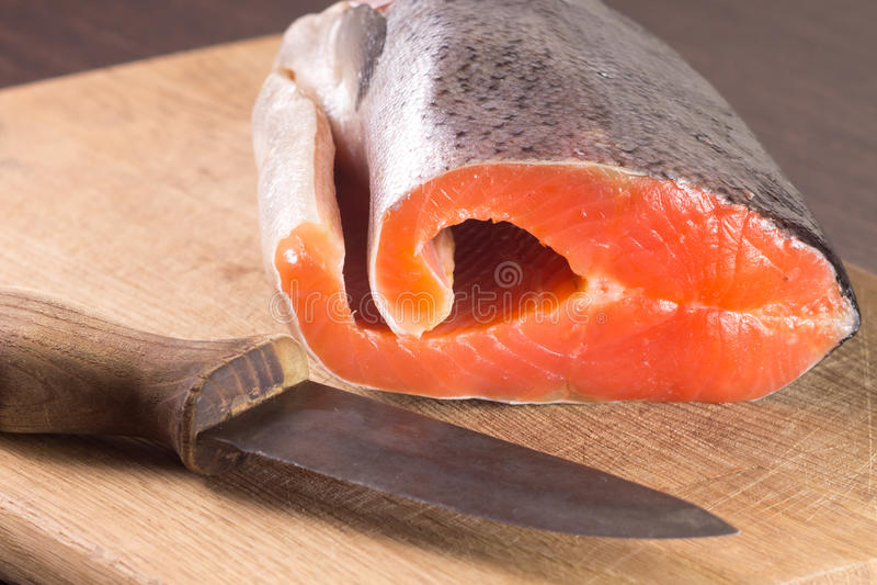 Salmones frescos con el cuchillo a bordo imagen de archivo