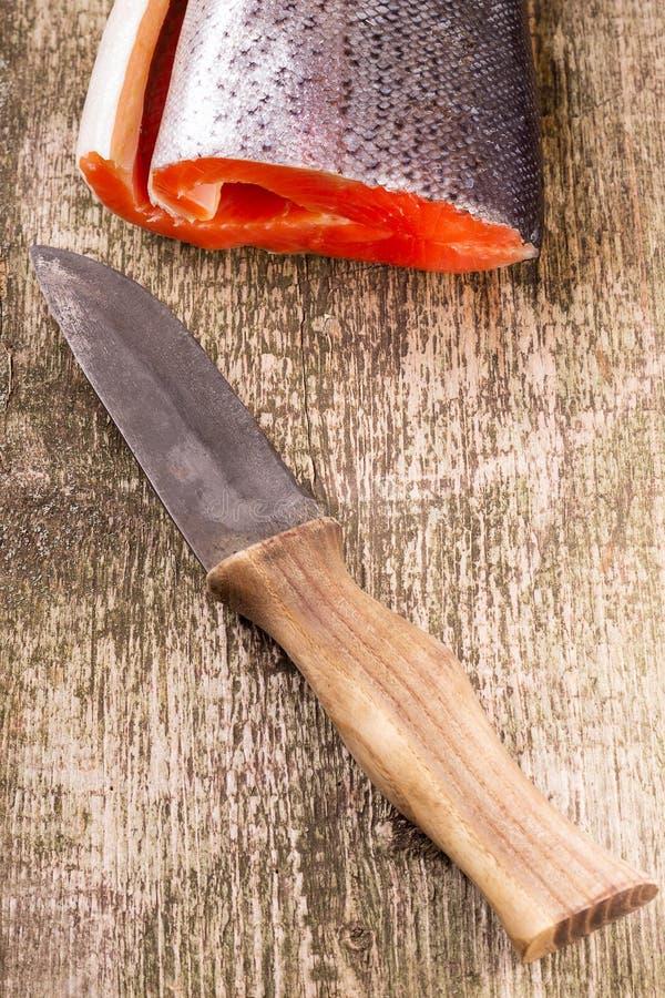 Salmones frescos con el cuchillo viejo en el tablero de madera imagen de archivo