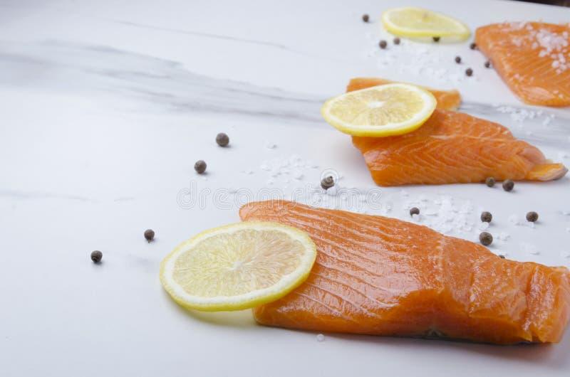 Salmones frescos con las rebanadas de limón y de pimienta en la tabla de mármol Primer de pescados imagen de archivo libre de regalías