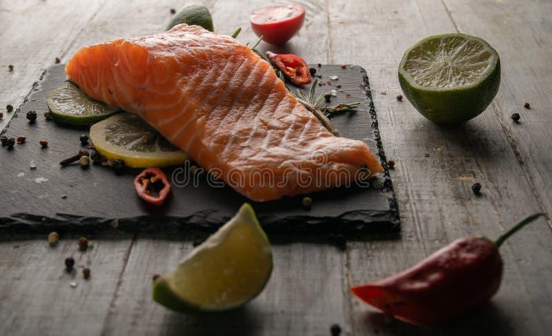 Salmones fritos con los condimentos con romero y limón y pimienta roja foto de archivo libre de regalías