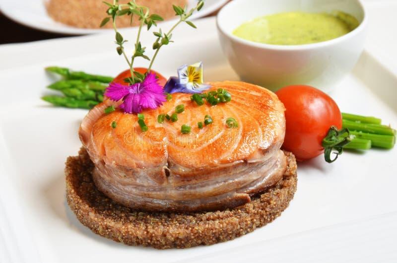 Salmones fritos con los granos rojos de la quinoa foto de archivo