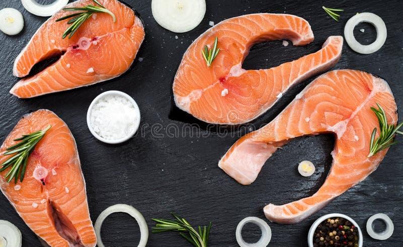 Salmones o trucha sin preparación crudos frescos, filetes de los pescados, en una sartén para cocinar, con la sal, la pimienta en fotografía de archivo