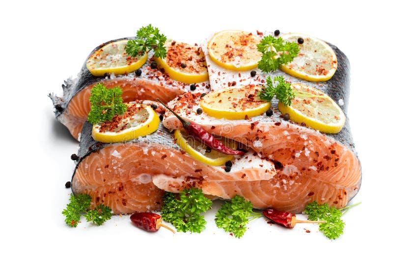 Salmones salados con el limón y las especias aislados en blanco imagen de archivo