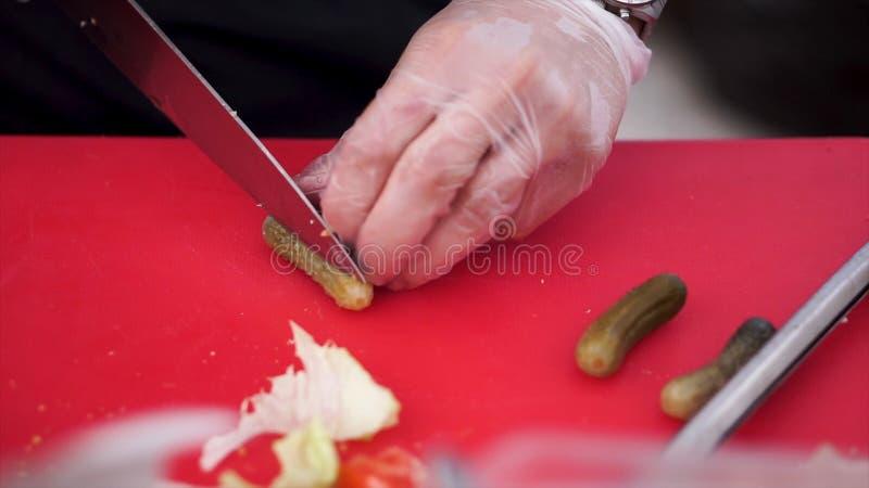 Salmouras do corte da faca na placa de madeira grampo O cozinheiro corta os pepinos conservados, faca nas mãos fêmeas, processo d imagem de stock