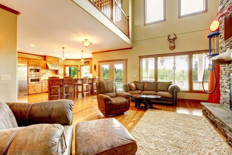 Salon avec la cheminée à haut plafond et en pierre et le sofa de cuir. photographie stock libre de droits
