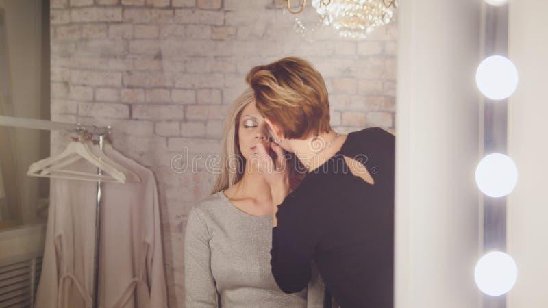 Salon de beauté - maquilleur et miroir proche modèle blond dans le vestiaire photographie stock