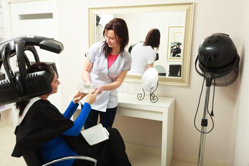 Salon de coiffure. Coiffeur donnant la cliente de femme de café de tasse. Équipement moderne. image libre de droits