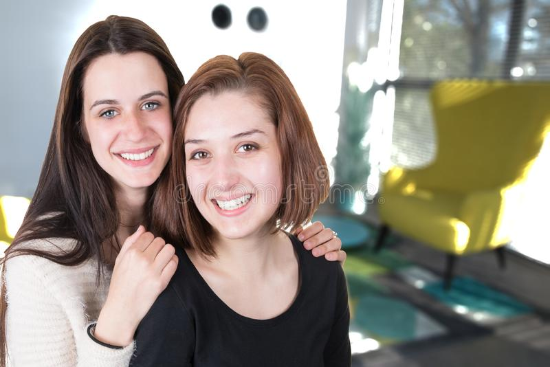Salon heureux de sourire de deux jeunes femmes dans une maison image libre de droits