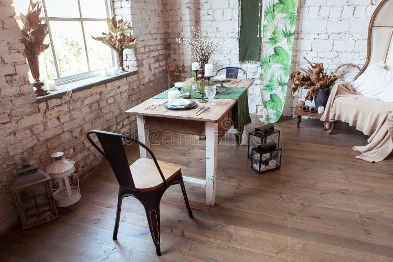 Salon moderne de grenier avec à haut plafond, sofa, mur de briques blanc vide, plancher en bois, accessoires de conception, table photo libre de droits