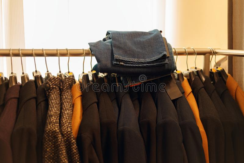 Salon shop. new coat and jeans on hangers in the boutique market royalty free stock image