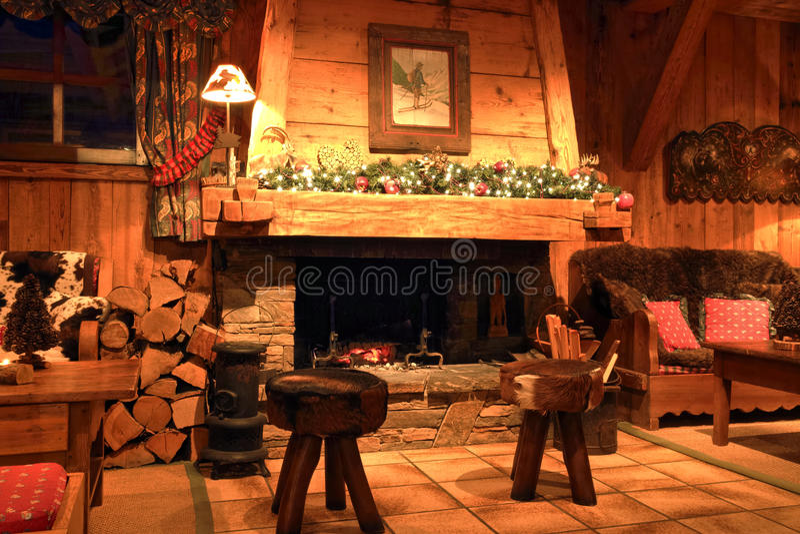 Salon traditionnel de chalet avec une cheminée brûlante en bois image libre de droits
