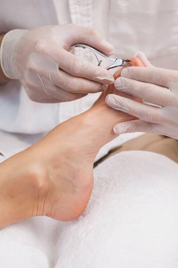 Salonarbeider die een spijkerclippers met behulp van stock foto's