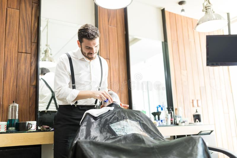 Salonarbeider die Scheermes met behulp van om Cliënt` s Gezicht te scheren stock afbeelding