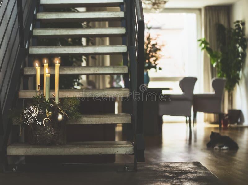 Salone accogliente con le scale al secondo piano, decorazione di inverno con le candele brucianti sui punti, finestra e gatto Vac immagini stock libere da diritti