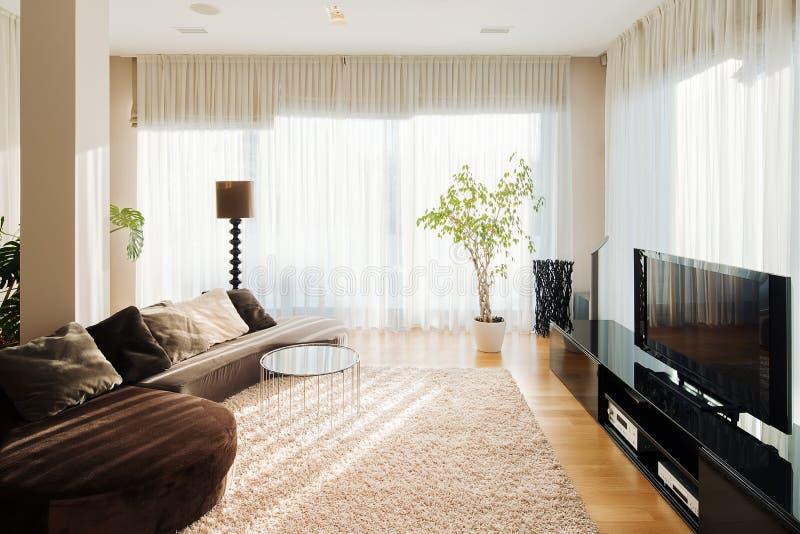 Salone comodo con il sofà ed il set televisivo lunghi fotografia stock libera da diritti