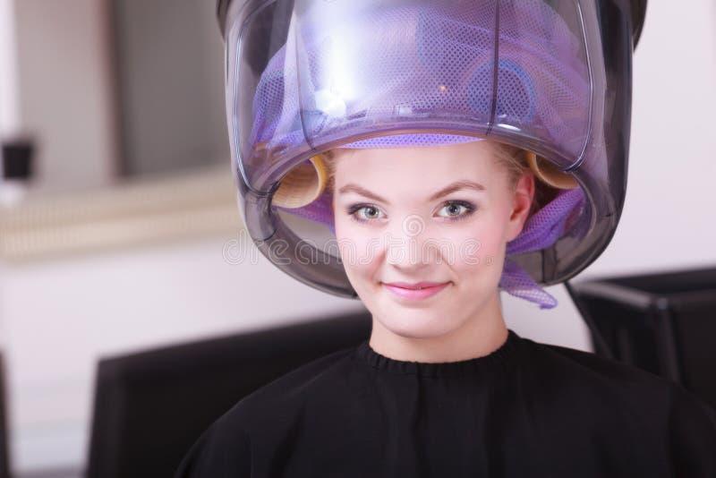 Salone di bellezza sorridente di lavoro di parrucchiere del hairdryer dei bigodini dei rulli dei capelli della donna immagini stock libere da diritti