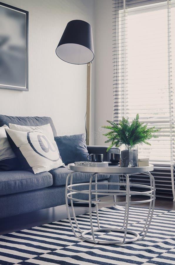 Salone moderno con il sofà blu e la tavola rotonda su tappeto immagini stock libere da diritti