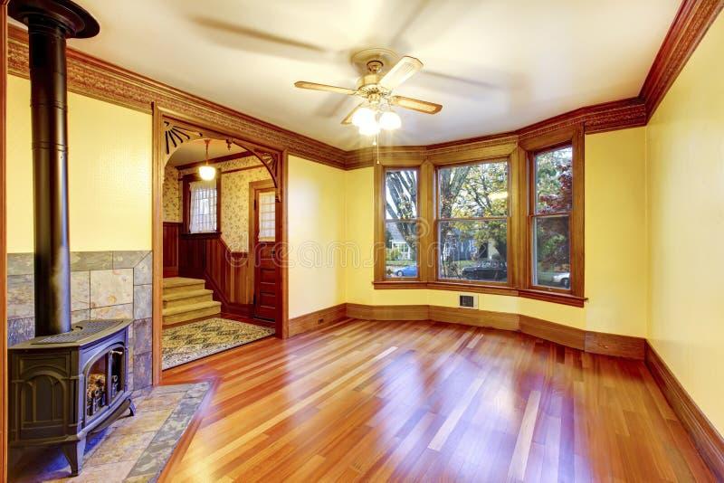 Salone non ammobiliato con il camino, il pavimento di legno duro e la pasta fotografia stock