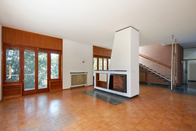 Salone vuoto con il camino, interno dell'appartamento in vecchia casa con il giardino immagini stock