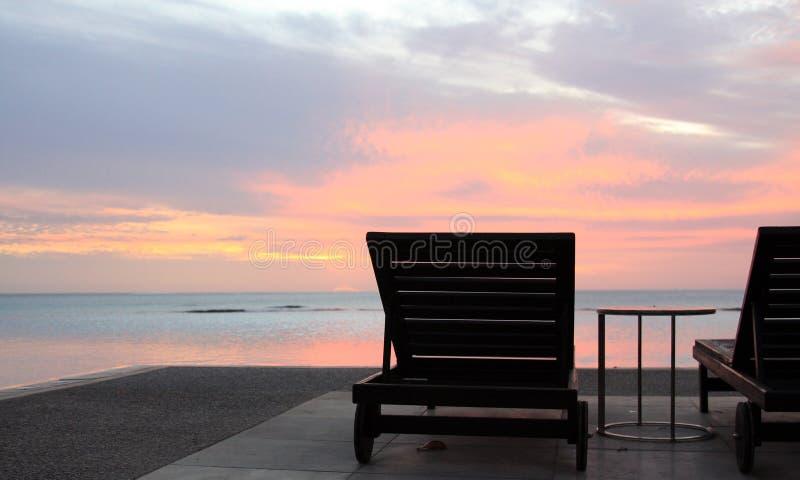 Salones de Sun que pasan por alto la piscina y la playa del infinito en la puesta del sol en un centro turístico tropical foto de archivo