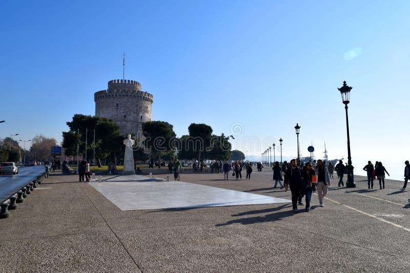 Salonicco, Grecia - 28 dicembre 2015: La gente che cammina nel lungomare di Salonicco, fondo bianco della torre immagini stock