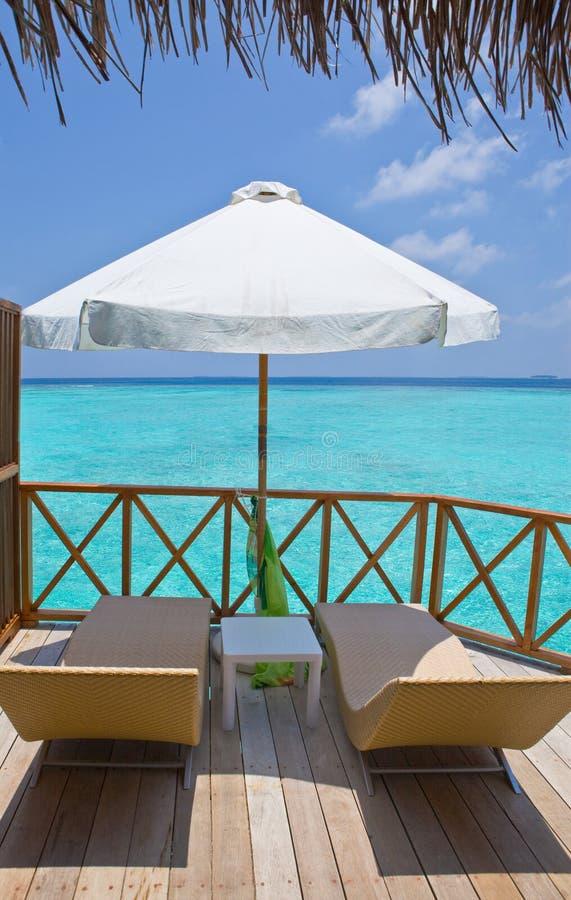 Salons de parasol et de cabriolet sur une terrasse de l'eau v image libre de droits