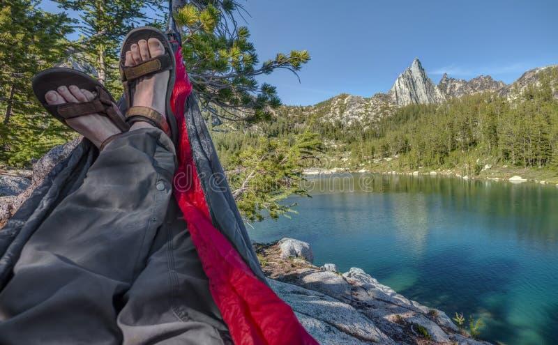 Salons de randonneur dans l'hamac au-dessus du lac alpin photos libres de droits
