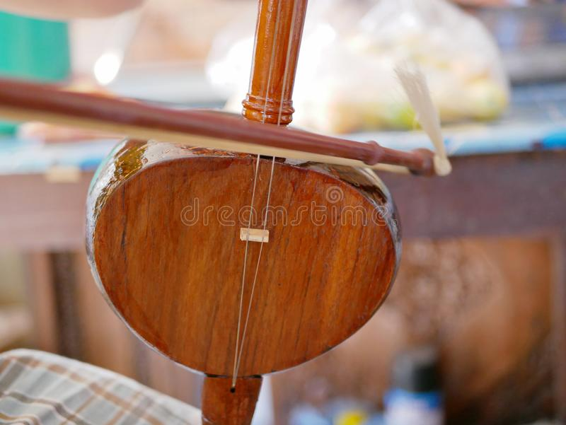 Salor being played, two or three-string spike fiddle used in the Lanna region or in the North of Thailand. Close up of Salor being played, two or three-string stock images