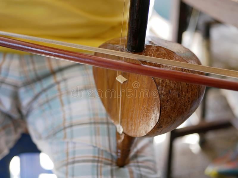 Salor being played, two or three-string spike fiddle used in the Lanna region or in the North of Thailand. Close up of Salor being played, two or three-string stock photography