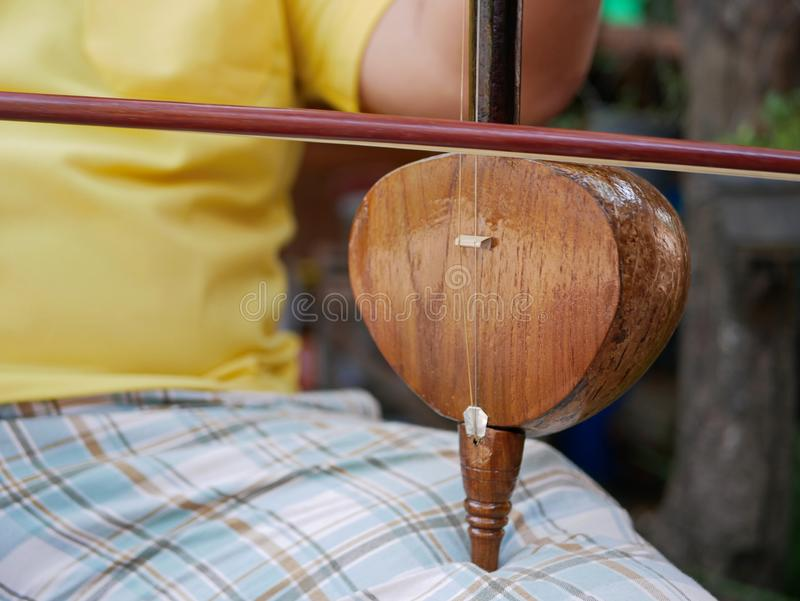 Salor, two or three-string spike fiddle used in the Lanna region or in the North of Thailand, being played. Close up of Salor being played, two or three-string royalty free stock images