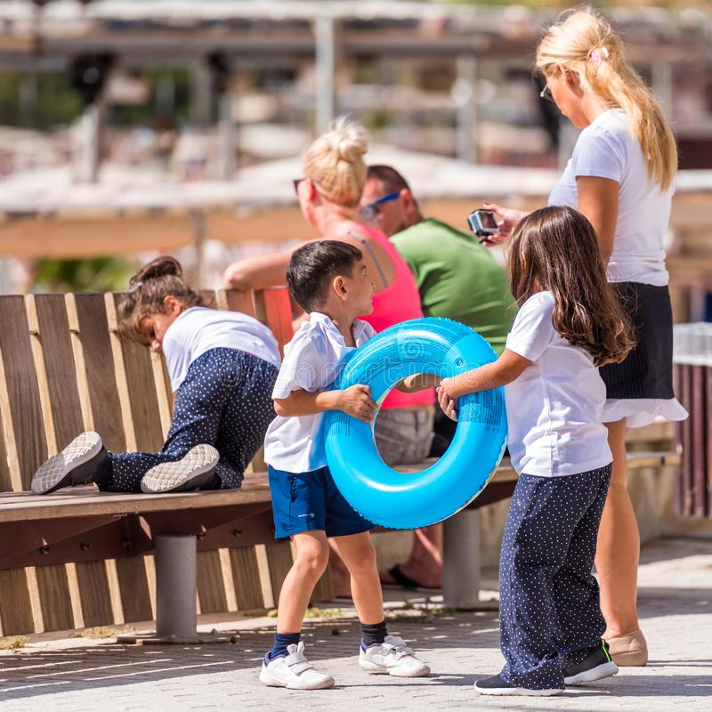 SALOU, TARRAGONA, SPAIN - SEPTEMBER 17, 2017: Children with a swimming circle on the waterfront. Close-up. royalty free stock image