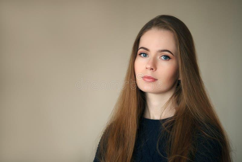 Salowy headshot szczęśliwa naturalna przyglądająca piękna kobieta w zmroku - błękitny puloweru beżu tło obrazy royalty free