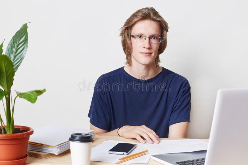 Salowy obrazek utalentowany fachowy męski urzędnik z modną fryzurą, jest ubranym widowiska i t koszula, siedzi przy stołem, wor zdjęcie stock