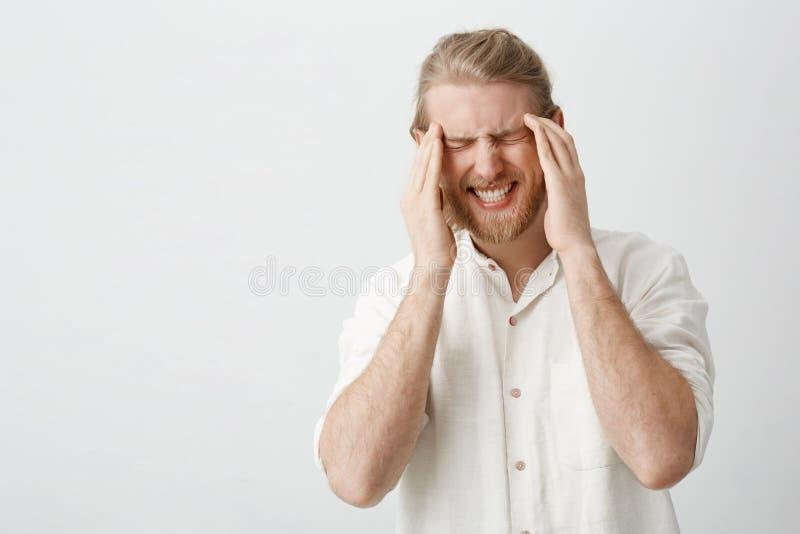Salowy portret caucasian blondynu mężczyzna z brody cierpieniem od migreny lub migreny, mienie dotyka na świątyniach zdjęcie stock