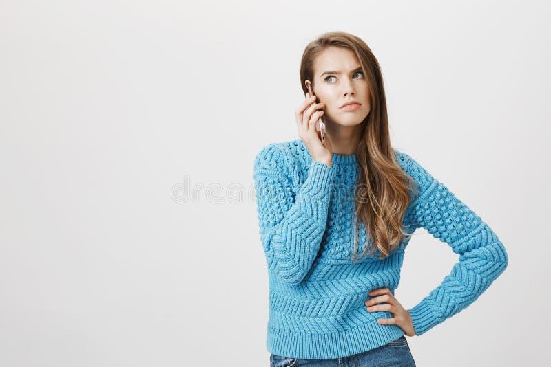 Salowy portret czeka dokuczająca i gniewna kobieta patrzeje na boku z blondynem podczas gdy trzymający smartphone blisko ucho, gd fotografia royalty free