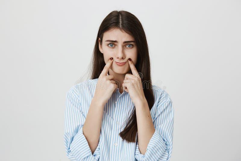 Salowy portret nieszczęśliwa i zaakcentowana kobieta z marszczyć brwi brwiami rozciąga usta z palcami wskazującymi robić ponuract zdjęcia stock