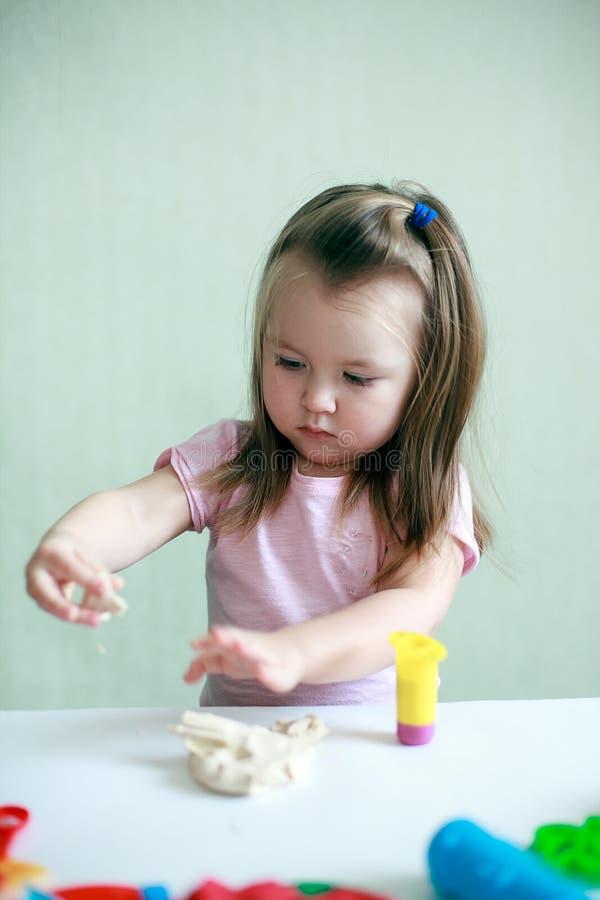 Salowy portret potomstwa 2 roku szczęśliwej uśmiechniętej caucasian dziecko dziewczyny bawić się z sztuki ciastem fotografia stock