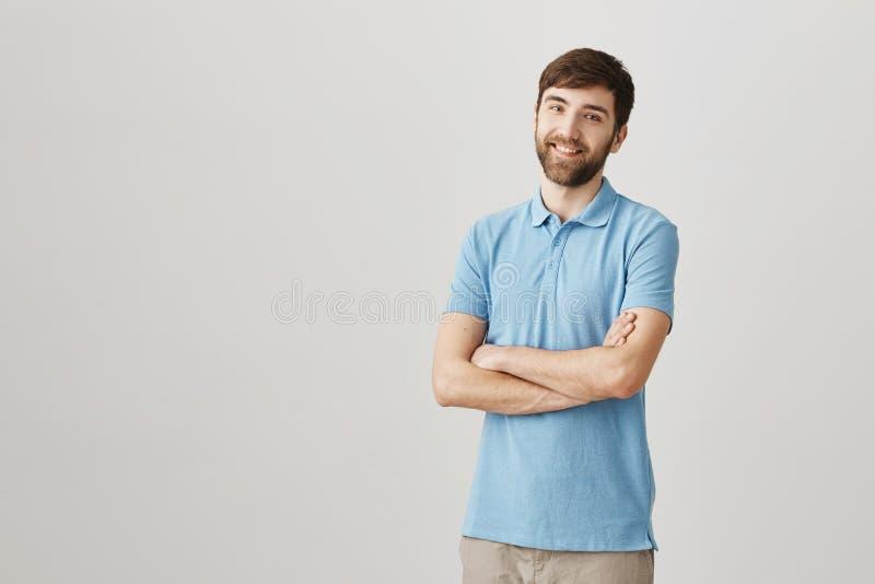 Salowy portret pozytywny przyglądający szczupły caucasian brodaty facet z rękami krzyżował na klatce piersiowej, ono uśmiecha się zdjęcia stock